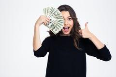 Ragazza che copre il suo occhio di banconote in dollari Fotografia Stock