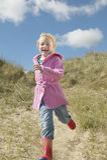 Ragazza che corre giù le dune di sabbia Fotografia Stock Libera da Diritti