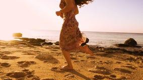 Ragazza che corre a piedi nudi alla spiaggia soleggiata