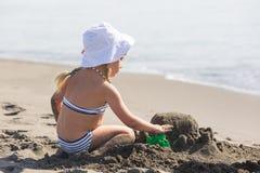 Ragazza che costruisce un castello della sabbia sulla spiaggia fotografia stock
