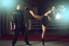 Ragazza che dà dei calci indietro alla gamba durante la pratica di kickboxing Fotografia Stock