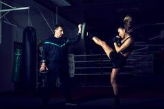 Ragazza che dà dei calci indietro alla gamba durante la pratica di kickboxing Immagini Stock
