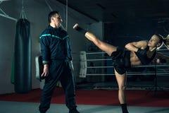Ragazza che dà dei calci indietro alla gamba durante la pratica di kickboxing Immagine Stock Libera da Diritti