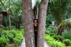 Ragazza che dà una occhiata attraverso il legno o due alberi Immagine Stock