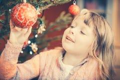 Ragazza che decora l'albero di Natale, tenente alcune bagattelle di Natale fotografia stock
