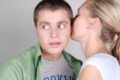 Ragazza che dice un segreto al suo ragazzo Immagine Stock