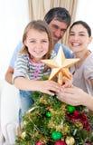 Ragazza che dispone una stella di natale sulla parte superiore di un albero Immagine Stock
