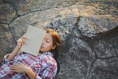 Ragazza che dorme con il libro su fondo di pietra Immagine Stock