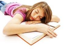 Ragazza che dorme con la sua testa su un libro aperto Immagine Stock