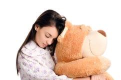 Ragazza che dorme con un grande orsacchiotto. Immagini Stock