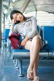 Ragazza che dorme nel corridoio aspettante dell'aeroporto Fotografia Stock