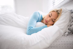 Ragazza che dorme tardi dentro sul fine settimana stanco a partire dalla settimana lavorativa lunga che riposa sul piumino di bia Fotografia Stock