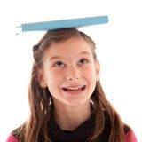 Ragazza che equilibra un libro sulla sua testa Fotografia Stock