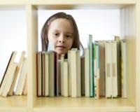 Ragazza che esamina i libri sullo scaffale per libri Immagine Stock Libera da Diritti