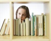 Ragazza che esamina i libri sullo scaffale per libri Fotografia Stock