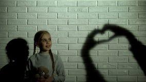 Ragazza che esamina l'ombra del cuore sulla parete e che abbraccia orsacchiotto, speranza e gentilezza immagini stock