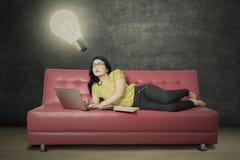 Ragazza che esamina lampada ed il computer portatile di usi Fotografie Stock Libere da Diritti