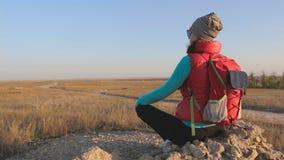 Ragazza che esamina tramonto in savana che si siede sulla roccia stock footage