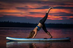 Ragazza che esercita yoga sul paddleboard nel tramonto sul lago scenico Velke Darko fotografia stock libera da diritti