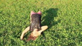 Ragazza che esercita yoga sul prato video d archivio