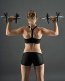 Ragazza che fa allenamento della spalla con le teste di legno Fotografia Stock