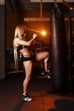 Ragazza che fa allenamento di pugilato nella palestra Combattente femminile che dà dei calci al punching ball Fotografie Stock Libere da Diritti