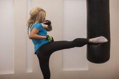 Ragazza che fa allenamento di pugilato nella palestra Punching ball femminile di moneta falsa del combattente Immagine Stock Libera da Diritti