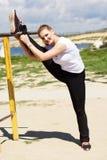 Ragazza che fa allungando esercizio vicino alla barra trasversale Immagine Stock Libera da Diritti