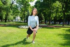 Ragazza che fa allungando gamba all'aperto nel parco Immagini Stock