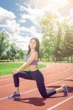 Ragazza che fa allungando gli esercizi sulla pista Fotografia Stock Libera da Diritti