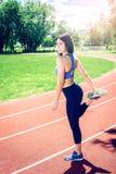Ragazza che fa allungando gli esercizi sulla pista Fotografia Stock