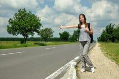 Ragazza che fa auto-stop sulla strada Immagine Stock