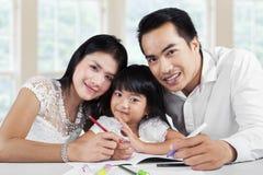 Ragazza che fa compito con i suoi genitori Fotografia Stock