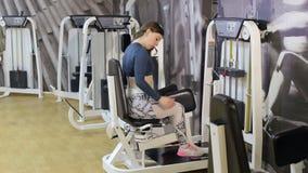 Ragazza che fa esercizio per le gambe su una macchina della stampa video d archivio