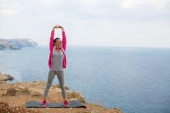 Ragazza che fa ginnastica di mattina sull'oceano della spiaggia Immagini Stock Libere da Diritti