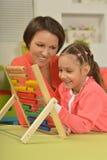 Ragazza che fa gli esercizi di per la matematica con la madre Fotografie Stock