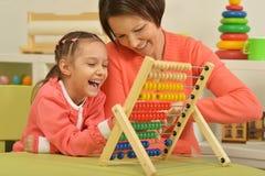 Ragazza che fa gli esercizi di per la matematica con la madre Fotografia Stock