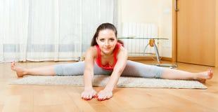 Ragazza che fa gli esercizi sulla stuoia a casa Fotografia Stock