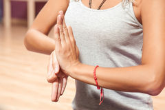 Ragazza che fa il primo piano speciale di posizione di yoga all'interno Immagine Stock