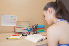 Ragazza che fa il suo lavoro Libri di scuola sullo scrittorio, concetto di istruzione Ragazza che fa le lezioni a casa Fotografie Stock Libere da Diritti