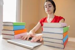 Ragazza che fa il suo lavoro Libri di scuola sullo scrittorio, concetto di istruzione Ragazza che fa le lezioni a casa Fotografia Stock