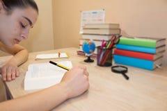 Ragazza che fa il suo lavoro Libri di scuola sullo scrittorio, concetto di istruzione Ragazza che fa le lezioni a casa Immagini Stock