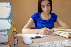Ragazza che fa il suo lavoro Libri di scuola sullo scrittorio, concetto di istruzione Ragazza che fa le lezioni a casa Fotografie Stock