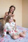Ragazza che fa l'amica dell'acconciatura a letto bedroom immagine stock libera da diritti