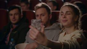 Ragazza che fa la foto del selfie con il ragazzo al cinema Coppie di amore che prendono foto stock footage