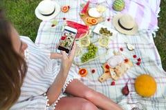 Ragazza che fa la foto dell'alimento al picnic Immagini Stock