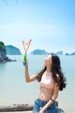 Ragazza che fa le bolle di sapone con la vista della spiaggia Fotografie Stock Libere da Diritti
