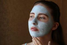 Ragazza che fa maschera cosmetica sul suo fronte Immagini Stock