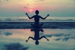 Ragazza che fa meditazione nella spiaggia dell'oceano Con la riflessione in acqua Fotografia Stock