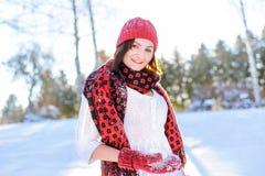 Ragazza che fa palla di neve e che smiing in camera nell'inverno Fotografia Stock
